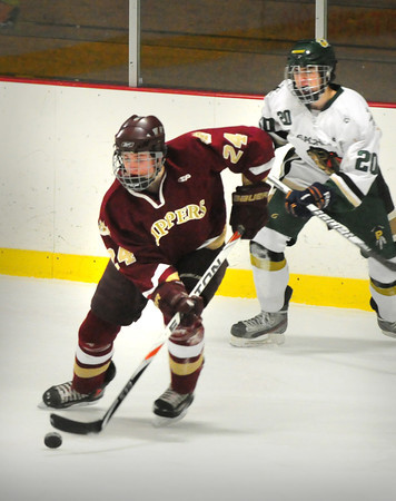 Haverhill: Newburyport's Andrew Williams moves the puck past Pentucket's Jeremy Binding. Bryan Eaton/Staff Photo