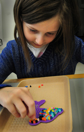 Salisbury: Brenna Coates, 7, puts Perler beads onto a template of a dolphin Tuesday afternoon at Salisbury Elementary School in the afterschool programs Explorations. Later they children would have the pieces ironed to melt into place then they could take them home to hang on a window or door for decoration. Bryan Eaton/Staff Photo