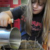 Newburyport: Michelle Gendron, 10, pours green tea and willow scented wax into jars at the Kelley School Teen Center. The children will be selling them along with items at the spring Newburyport Farmer's Market. Bryan Eaton/Staff Photo