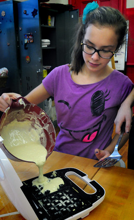 "Newburyport: Julia Vachon, 11, pours waffle batter into a griddle at the Kelley School Youth Center for ""Wacky Waffle Wednesday."" The children also made lemon scented sugar scrubs, which give hands a fresh cleansing which they're trying to perfect to possibly sell at the Newburyport Farmer's Market in the spring. Bryan Eaton/Staff Photo"