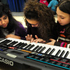 Amesbury: Shauna Roaf, 9, creates a song on the keyboard in Alicia Harlov's music class at Amesbury Elementary School before instruction began as the rest of the class was setting up their instruments. Listening are Alicia Cedeno, 10, left and Callie Beauparlant, 9, right. Bryan Eaton/Staff Photo