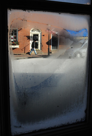 Newburyport: A pedestrian walks briskly down Liberty Street in Newburyport in a photo shot through a frosty window pane from Starbucks Coffee in Market Square on Thursday morning. Bryan Eaton/Staff Photo