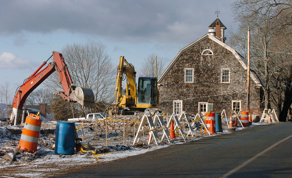 Newbury: Heavy equipment cleans up the debris Tuesday from the demolition of the home and one of the barns over the weekend. Bryan Eaton/Staff Photo