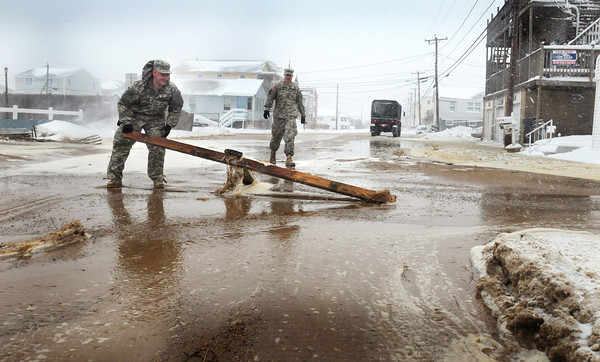 Salisbury: National Guard crew from Methuen clear debris that came in with loads of sand on North End Boulevard in Salisbury. The roadway remained open, though drivers needed to take caution. Bryan Eaton/Staff Photo
