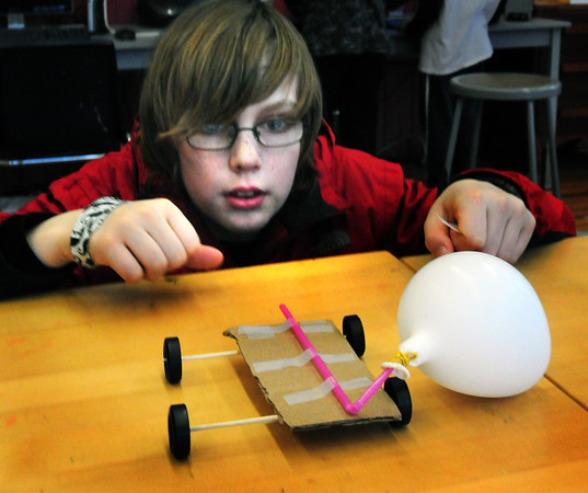 Newburyport: Luke Young, 11, releases a prototype race car powered by the air coming out of a balloon he blew up. His team is one of several at the Kelley School Drop-In Center participating in the upcoming Destination Imagination competition. Bryan Eaton/Staff Photo
