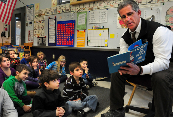 """Amesbury: Amesbury police detective Robert Wile reads """"The Cat in the Hat"""" to first-graders at Cashman Elementary School on Monday for Read Across America where guests readers come to schools. Bryan Eaton/Staff Photo"""