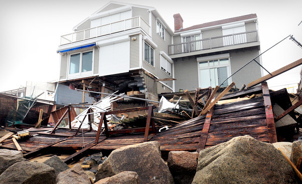 Newbury: A metal-framed protective wall with railroad ties gave way during last week's storm damaging this home and about ten others, two falling off their foundations. Bryan Eaton/Staff Photo