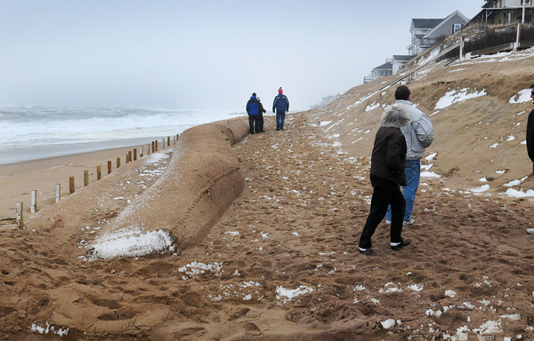 Newbury: People check out the situation at Plum Island Center last night at 5:00pm, roughly two hours before the high tide. Three piles of the giant sandbags to the left of photo. Bryan Eaton/Staff Photo