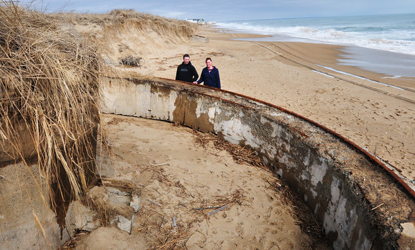 Salisbury: Chris Stiles, and Kelly Burns from Merrimac check out World War II era 155mm gunnery emplacements that were uncovered during last weekend's storm at Salisbury Beach State Reservation. The structures have been sited over the years, depending on the shifting sands. Bryan Eaton/Staff Photo