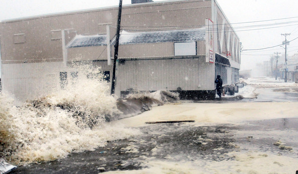 Salisbury: A man photographs the waves breaching sand piles on Oceanfront North at Salisbury Beach before police moved him along. Bryan Eaton/Staff Photo