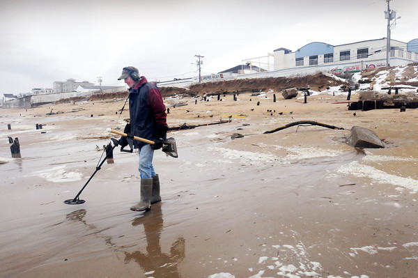 Salisbury: Badger Baird of Newington, NH scans for metal as new hunting grounds opened up at the head of Broadway at Salisbury Beach Center after the storm exposed remnants of precious structures including pilings from the old Frolics. Bryan Eaton/Staff Photo