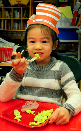 "Salisbury: Brianna Pham, 5, digs in to her ""green eggs and ham"" at Salisbury Elementary School on Monday afternoon. Kindergartner's in Kathleen Orroth's class were having a birthday celebration for Dr. Seuss. Bryan Eaton/Staff Photo"