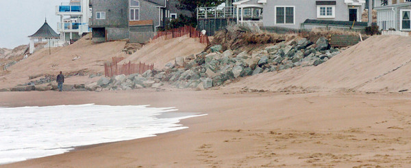 Newbury: A person walks along Plum Island sand as the beach south of the center has reopened. Some of the rocks dumped there to protect homes from erosion have been covered with sand. Bryan Eaton/Staff Photo