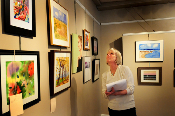 Newburyport: Susan Spellman looks over entries as she judges the Young and Budding Artists show. Bryan Eaton/Staff Photo