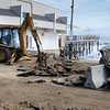 Salisbury: Areas at Salisbury Beach Center are still closed for public safety reasons. Ray Cote of the Salisbury DPW cleans up asphalt and other debris that was damaged in last week's storm on Wednesday. Bryan Eaton/Staff Photo