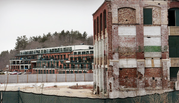 Amesbury: The unfinished portion of condominiums at Hatter's Point, at right, contrast with the occupied units at left. Bryan Eaton/Staff Photo