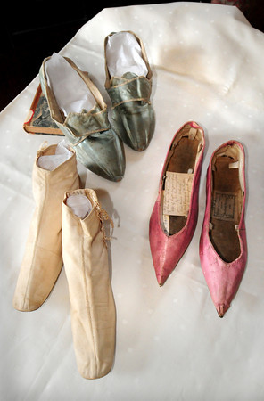 Newburyport: Clockwise, from top, from 1765, the pink shoes from 1805 wedding shoes for Newburyporter Margaret Lord and the white were dancing shoes from around 1850. Bryan Eaton/Staff Photo