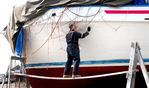 Newburyport: Joe Grady paints the Challenger party boat at drydock next to the Black Cow Tap and Grille on Newburyport's waterfront Monday afternoon. The ship operates out of Bridge Marina in Salisbury where it will be heading soon as the boating season is close to resuming. Bryan Eaton/Staff Photo