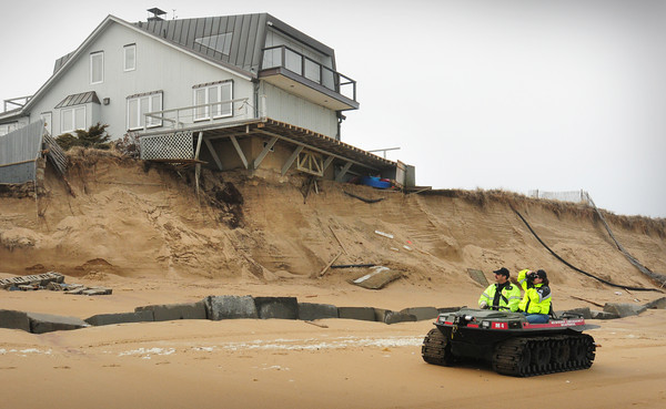 Newbury: Newbury police Sgt. Patty Fisher, right, photographs damaged homes on Plum Island with Det. John Lucey on Monday afternoon. Bryan Eaton/Staff Photo