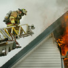 Amesbury: Firefighters on the Newburyport Fire Department's ladder truck approach a fire on 9 Huntington Street in Amesbury to cut a hole in the roof to vent the fire. Several fire departments were on hand to assist Amesbury in the two-alarm fire late Tuesday morning. Bryan Eaton/Staff Photo