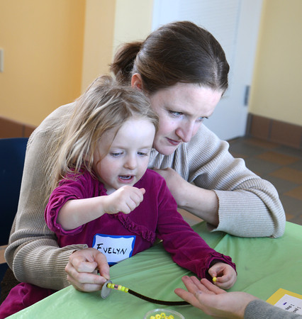 Newbury: Evelyn Helsel, 3, and her mom Carolyn make braclets at the Eco Games Free-for -All at the Mass Audubon's Joppa Flats Education Center Sunday morning. The event included hands on programs centered around ocean creatures, shore birds and sea level rise. Jim Vaiknoras/staff photo