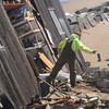 Newbury: A demolition worker removes hazardous material from 41 Annapolis Way on Plum Island, the house sustained catastrophic damage Friday and was demolished Saturday afternoon. Jim Vaiknoras/staff photo