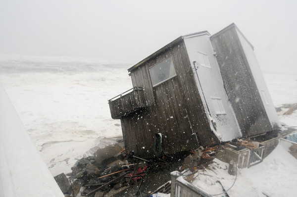 Newbury: Waves pound a damaged house at 41 Annapolis Way on Plum Island. The high tide from the storm knocked the ouse off it's foundation. Jim Vaiknoras/staff photo