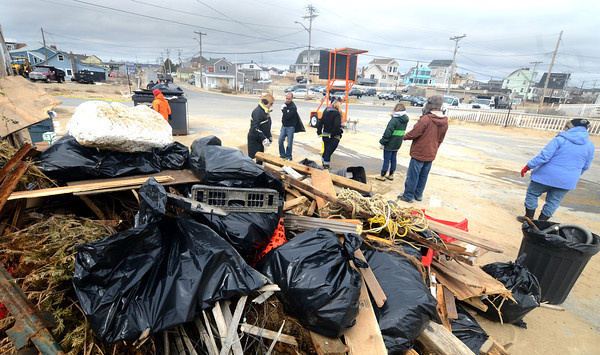 Newbury: Employees of TD Bank pile debris they collected on Plum Island at the Central Parking lot. A group of about 40 people pitch in to clean up the beach Monday morning. Jim Vaiknoras/staff photo