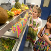 Seabrook: First graders Aubrey Thompson and Alexia Pontes pick up their Polynesian lunch at the Seabrook Elementary at the First Annual Seabrook School District Luau Friday. Jim Vaiknoras/staff photo