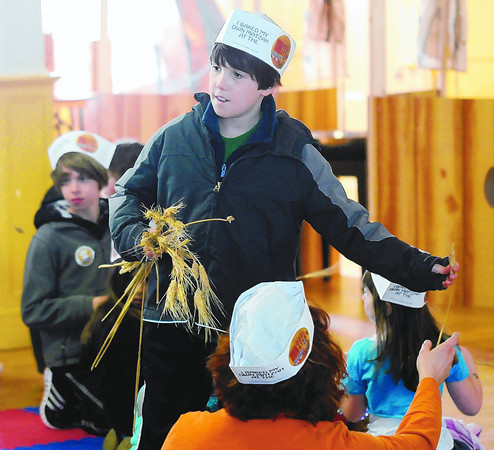 Newburyport: Casey Wanatick, 10, hands out wheat at a program Sunday at Ahavas Achim. The event put on by Travelling Matzah Bakery taught kids to make Matzah from scratch. Jim Vaiknoras/staff photo