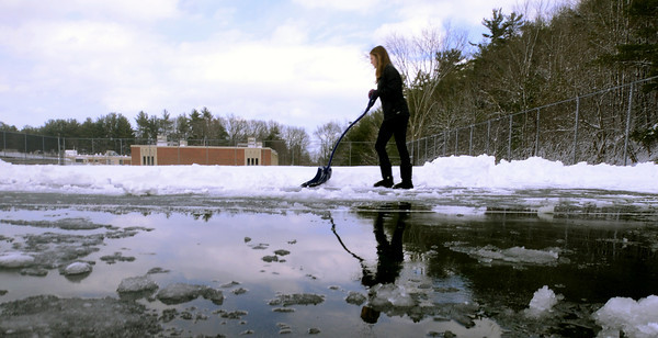 Amesbury: Olivia King shovels the tennis courts at Amesbury high school Wednesday afternoon. King along with the rest of the boys and girls teams traded their rackets for shovels for their first day of spring practice. Jim Vaiknoras/staff photo
