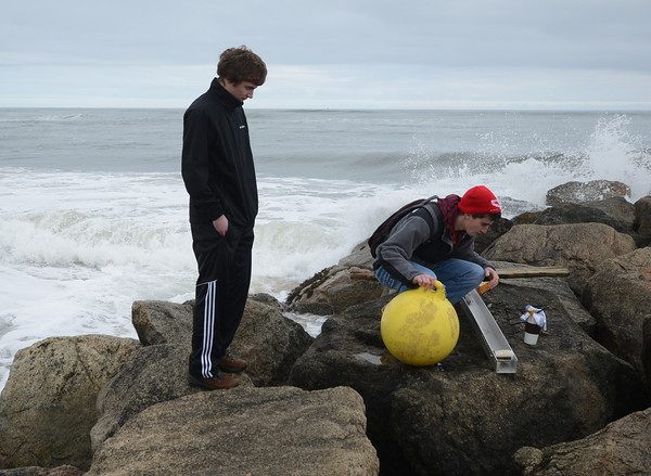 Newbury: Newburyport high students Chris Orlando and James Nutter gather up their equiptment on the center grion on Plum Island after measuring the amount of energy that can be harnessed by the wave action in the ocean as part of their science fair project. Jim Vaiknoras/staff photo