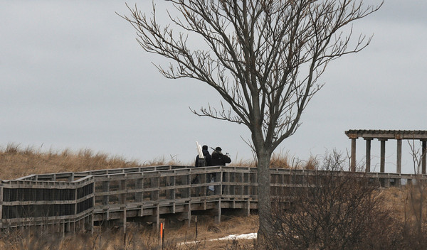 Newbury: Two fishermen walk down the boardwalk on Plum Island Point early Sunday afternoon. Jim Vaiknoras/staff photo