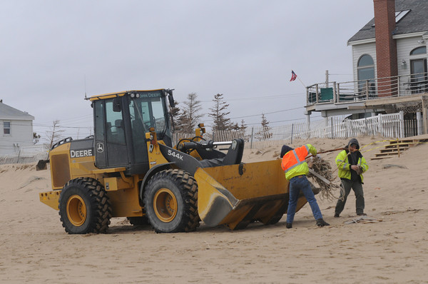 Newbury: Volunteers use a front end loader to remove debris on Plum Island. A group of about 40 people pitch in to clean up the beach Monday morning. Jim Vaiknoras/staff photo