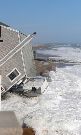 Newbury: 31 Annapolis Way on Plum Island ,which fell over early Saturday morning, is pounded by the surf at high tide later Saturday. Jim Vaiknoras/staff photo