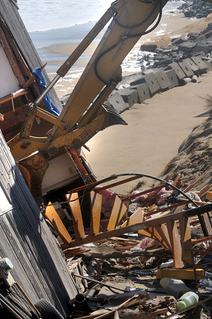 Newbury: An excavator removes a staircase from 41 Annapolis on Plum Island as it is  demolished Saturday due to damage from Friday's storm. Jim Vaiknoras/staff photo