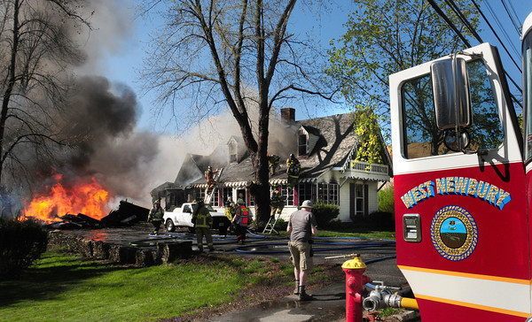 West Newbury: Firefighters direct their efforts to the house at 230 Main Street in West Newbury after the adjoining barn was lost. Bryan Eaton/Staff Photo