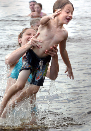 Amesbury: Kristjan Koper, 6, of Amesbury gets a toss from his mother, Koren, as the two cool off at Lake Gardner Beach in Amesbury yesterday afternoon. Bryan Eaton/Staff Photo