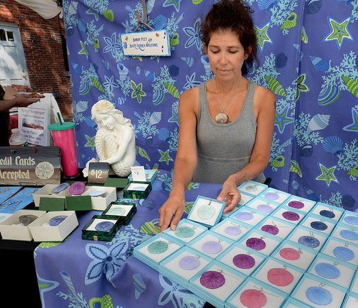 BRYAN EATON/Staff photo. Kat Couree tends the booth of artist Amy Sciuto at the Inn Street Artisan's Festival. Sciuto colors sand dollars from Plum Island then encloses them in glass.