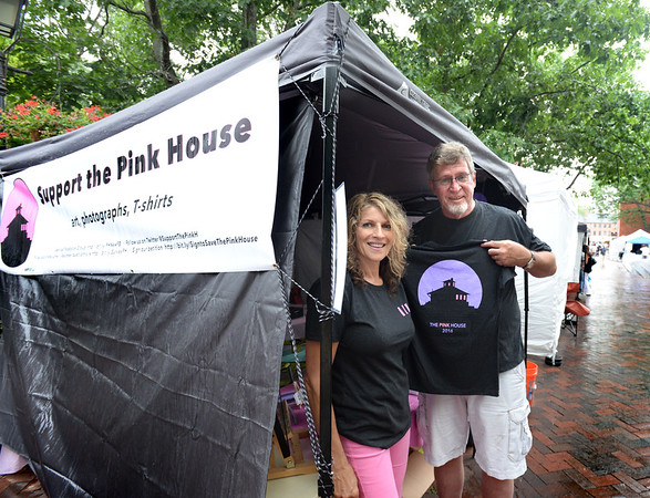 """Bryan Eaton/Staff photo. Rochelle Joseph, left, and Eric Hoover and their group trying to save """"the pink house"""" on Plum Island Turnpike from demolition have a booth on Inn Street selling various items, including t-shirts to raise funds."""