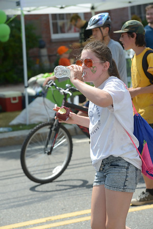 JIM VAIKNORAS/Staff photo.Annie Silliker has a drink and an apple as she marches with The Workshop in the Woods  during the Annual Yankee Homecoming Parade.