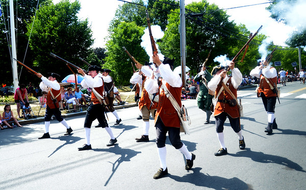 JIM VAIKNORAS/Staff photo. The Fife and Drum Corps of the Acton Minute Company fire their muskets on High Street during the Yankee Homecoming Parade.