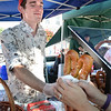 "BRYAN EATON/Staff photo. Rijard Bergeron, manning the ""When Pigs Fly"" booth in Market Square sells a Bavarian pretzel."