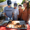 BRYAN EATON/Staff photo. Young volunteers at the hot dog and hamburger tent at Kids Day in the Park are, from left, Jacob Grossi-Hogg, Zach Lever, Luke Grossi-Hogg and Taylor Lever.