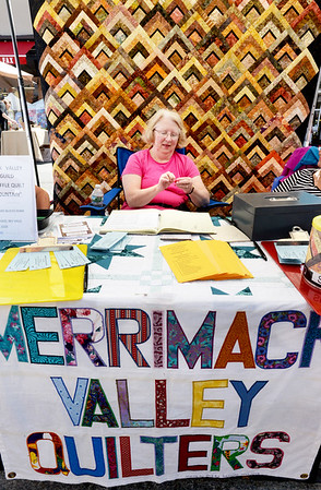 """BRYAN EATON/Staff photo. Beverly Valle of North Andover and member of the Merrimack Valley Quilters works below a quilt the group made for a raffle at the Market Square Craft Show. The drawing will be made at their Quilt Show """"Autumn Splendor"""" at the Hope Church on October 1."""