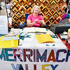 "BRYAN EATON/Staff photo. Beverly Valle of North Andover and member of the Merrimack Valley Quilters works below a quilt the group made for a raffle at the Market Square Craft Show. The drawing will be made at their Quilt Show ""Autumn Splendor"" at the Hope Church on October 1."