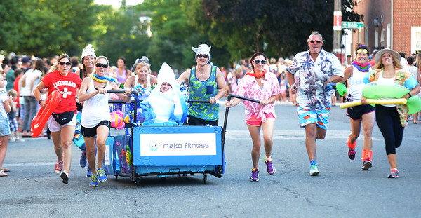 JIM VAIKNORAS/Staff photo. The Meko Fitness run their shark and beach themed bed makes it's down Federal Street in the annual Lions Club Bed Race.