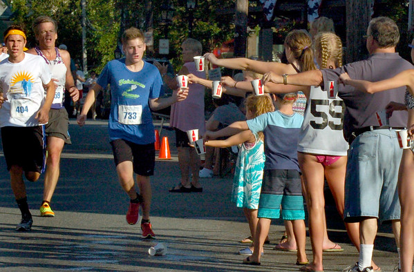 BRYAN EATON/Staff photo. Volunteers hand out water to the runners in front of the Starboard Galley on Water Street.