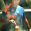 BRYAN EATON/Staff photo. Eric Lever, co-owner of Latitudes Sports Club in Salisbury, which provided hot dogs and hamburgers for Kids Day in the Park, is literally in the heat of the things as flames flare from cooking the burgers.
