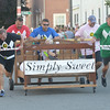 JIM VAIKNORAS/Staff photo. The Simply Sweet team burn off some calories as it raced down Federal Street in the annual Lions Club Bed Race.
